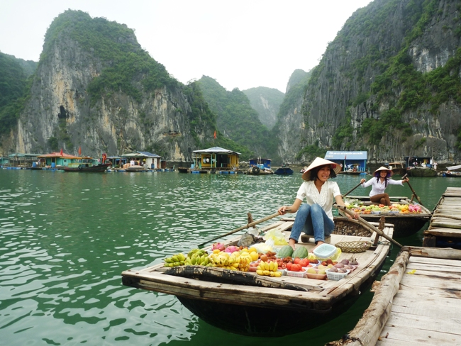 Woman selling fruits from a boat in Halong Bay Village, Vietnam